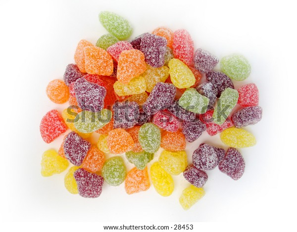Sour fruit candies scattered on a white background.