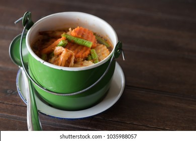 Sour soup made of Tamarind Paste in green cup on brown table, Thai food
