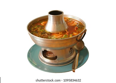"""Sour soup made of tamarind paste in hot pot. In white background. Thai menu call """"Kangsom"""""""