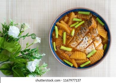Sour soup made of tamarind paste mixed with papaya , long bean and tilapia , Thailand food.