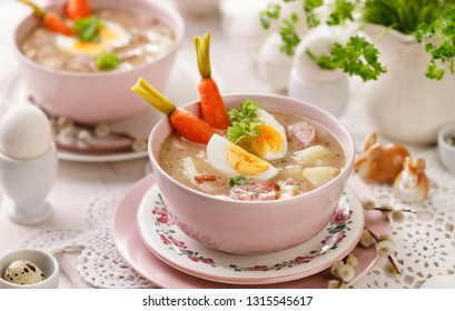 The sour soup (Żurek), polish Easter soup with the addition of sausage, hard boiled egg and vegetables in a ceramic bowl. Traditional Easter dish in Poland