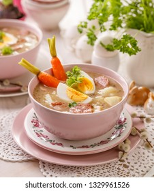 The sour soup (Żurek), polish Easter soup with the addition of sausage, hard boiled egg and vegetables in a ceramic bowl.  Traditional Easter food in Poland