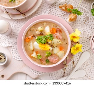The sour soup (Żurek), polish Easter soup with the addition of sausage, hard boiled egg and vegetables in a ceramic bowl, top view. Traditional Easter dish in Poland