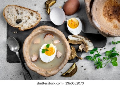 The sour soup (Zurek) made of rye flour with smoked sausage and eggs served in bread bowl. Traditional polish sour rye soup, popular Easter dish