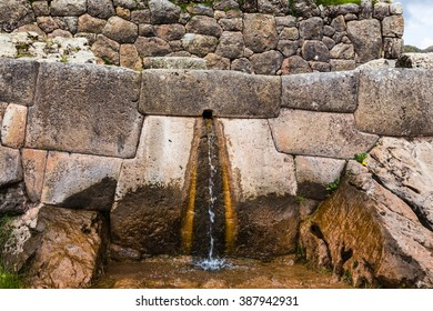 Source of water in a small stone in the Inca vein building in the province of Cusco, Peru