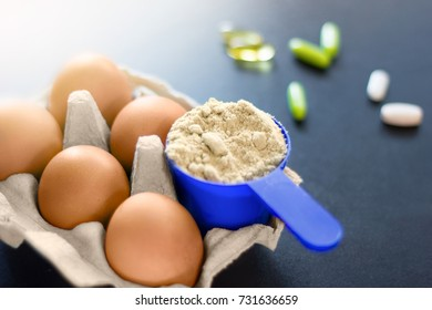 Sources of protein. Tray of eggs with whey protein powder in blue plastic scoop. Pills on dark background.