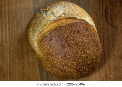 Sourdough bread on antique dough board. It is made by fermenting dough using naturally occurring lactobacilli and yeast. It has a mildly sour taste not present in most breads made with baker's yeast.