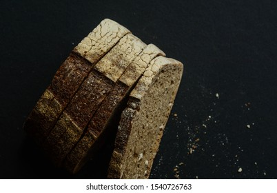Sourdough brown bread cut in slices on black background