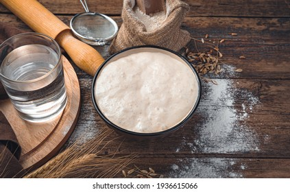 Sourdough, flour, water on a brown background. Yeast dough. The concept of making bread.