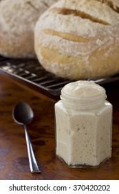 Sourdough starter fermenting and starts to ripen. Sourdough bread in background. Non Sharpen