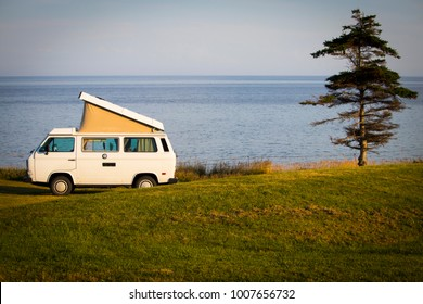 Souris, Prince Edward Island, Canada: July 18, 2018:  A Westfalia camper is parked alone in a grass field next to a single tree