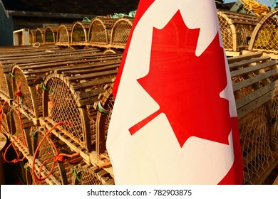 Souris, Prince Edward Island, Canada-July 17, 2017: Canadian lobster traps are stacked on the Souris Harbor Dock next to a Canadian flag is during the 2017 summer season.