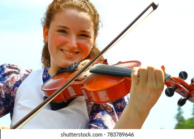 Souris, Prince Edward Island, Canada-July 18, 2017: A young woman playing the fiddle in a public park in Souris, PEI Canada in July for fun.