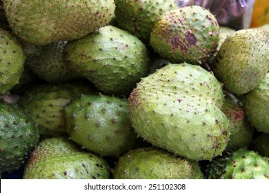 Soursop fruit piled high at a market stall in the Caribbean