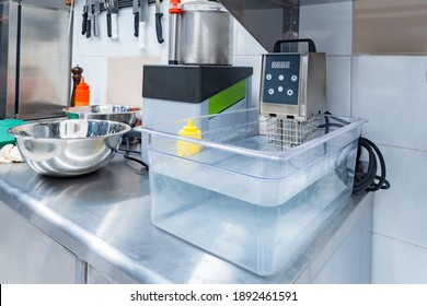Sous vide cooking device in restaurant kitchen. Fragment of a kitchen table from a restaurant. Container with water and a sous vide device in foreground. Using sous vide equipment in cooking
