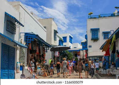 Sousse / Tunisia — August 23, 2018: lively street in Medina of Sousse, a medieval district with its traditional white and blue houses and carved balconies. The quarter is a popular tourist attraction