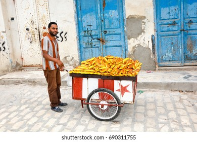 SOUSSE,TUNISIA - JUNE 30,2016:Seller a man carries on an old cart with fresh bread for sale at the Bazaar in the old city of Medina