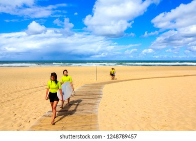 SOUSTON, FRANCE - AUGUST 3rd, 2018 : young surfer-girls carrying their surfer board while walking on the wooden jetty at the beach at the French Atlantic coast