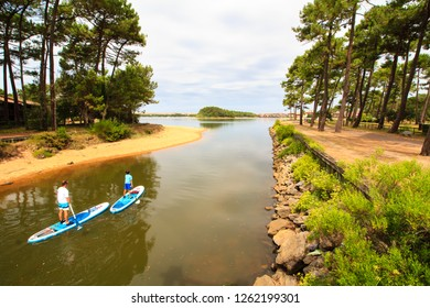 SOUSTONS, FRANCE - AUGUST 8, 2018 : Father and son practicing standup paddle boarding on the Soustons Lake, French Atlantic coast.