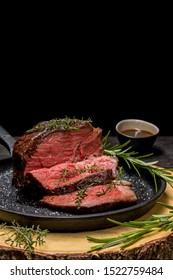 Sous-vide grilled beef steak with herbs in cast-iron skillet on wooden plate. Black background with copy space