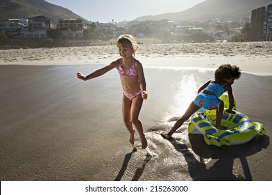 South Africa, Cape Town, two girls (6-10) playing with inflatable toy on sandy beach, smiling