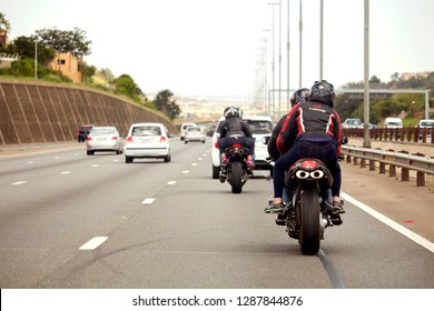 South Africa, Johannesburg - 12 January, 2019: The back view of the motorbikes and cars driving on the road. The traffic on the way to Joburg.