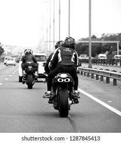 South Africa, Johannesburg - 12 January, 2019: Close-up back view of the motorcyclists driving on the road. The traffic on the way to the Joburg. The black and white image.