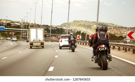 South Africa, Johannesburg - 12 January, 2019: The motorbikes and cars driving on the road. The traffic on the way to Joburg. The back view. South African hills background.