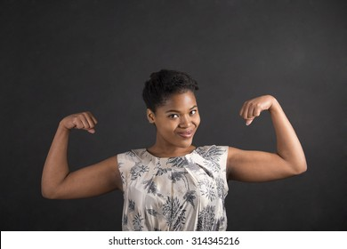 South African or African American black woman teacher or student with strong muscular arms standing against a chalk blackboard background inside