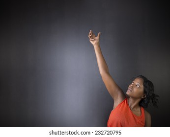 South African or African American woman teacher or student with hand reaching up on chalk black board background