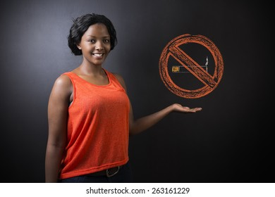 South African or African American woman teacher or student displaying a no smoking sign