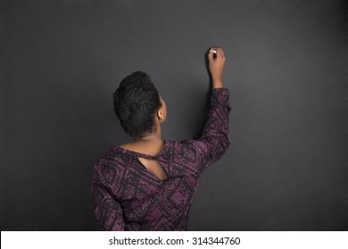 South African or African American woman teacher writing on chalk black board background inside