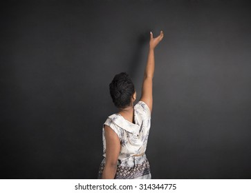 South African or African American woman teacher or student with hand reaching up on chalk black board background inside