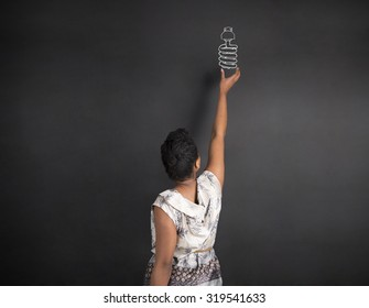South African or African American woman teacher or student with hand reaching up to a globe on chalk black board background inside