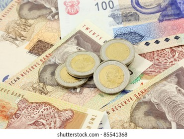 South African Currency - A Pile of Five Rand Coins on different denomination Rand Notes