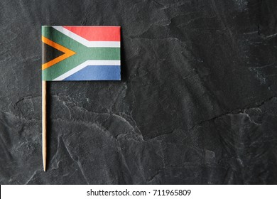 A South African flag toothpick on a black slate background.