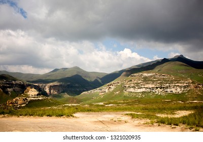 South African landscape. Drakensberg mountains before the rain. Golden Gate Highlands National Park. The green grass covered valley and mighty mounts under the rainy cloudy sky. Wilderness.