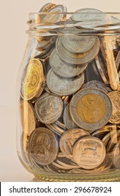 south african silver and gold minted coins in a glass jar mixed amounts of rands