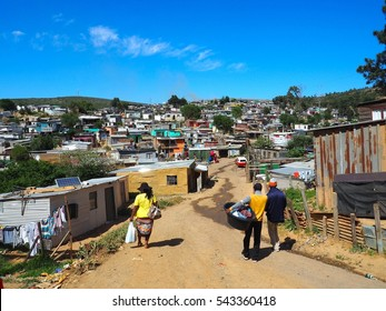 South Africans walking on the street of informal settlements,huts made of metal in the Township or Cape Flats of Stellenbosch,Cape Town,South Africa with mountain, blue sky and clouds background, Slum