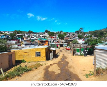 South Africans walking on the street of colorful informal settlements, huts made of metal in the Township or Cape Flats of Stellenbosch,Cape Town,South Africa with blue sky and clouds background, Slum