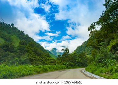 South America. Ecuador. Andes mountains covered with greenery. An asphalt road leads to Andes mountains. Landscape of Ecuador. Sightseeing In Ecuador.
