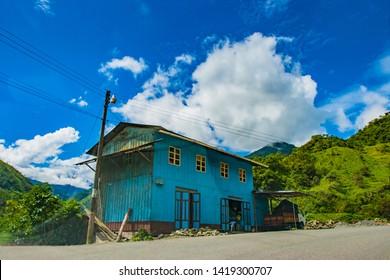 South America. Ecuador. Old roadside building at the bottom of the Andes. Green Andes mountains. Mountain landscape of Ecuador. Tours to Ecuador. 06.05.2006