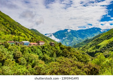 South America. Ecuador. Separately located village at the height of the Andes. Ecuadorian rural settlement. Andes mountains greenery covered with cloudy tops. Mountain landscape of Ecuador. Tours