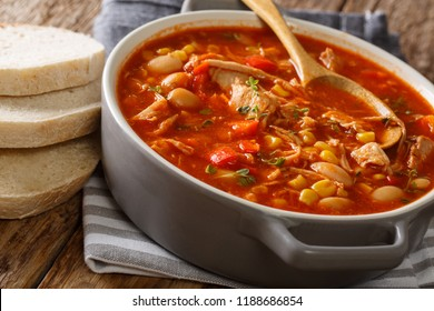 South American food Brunswick Stew pulled meat with vegetables on chicken broth and barbecue sauce close-up in a pot on the table. horizontal