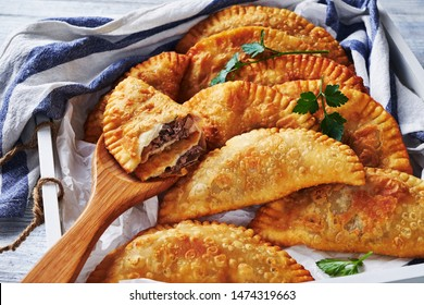 South american food: crispy fried empanadas with ground beef stuffing served on a white serving tray on white wood background with a kitchen dish towel, close-up