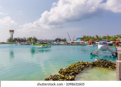 South Ari Atoll, Dhidhoofinolhu, Maldives - May 3 2018: Maldives airline seaplane near tropical islands in blue sea. Transmaldivian airlines in Male airport