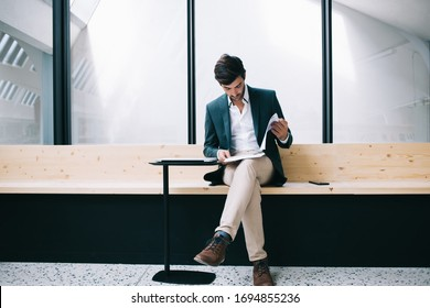 South Asian businessman in formal clothing reading executive tutorial suiting in modern workspace, Indian male trader checking information from financial paper report concentrated on planning
