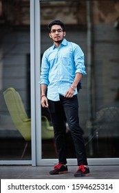 South asian indian male student wear eyeglasses and casual posed outdoor.