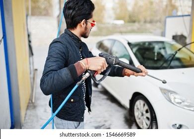 South asian man or indian male washing his white transportation on car wash.