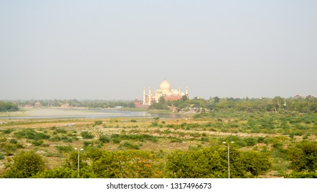 """South bank of Yamuna river and distant Taj Mahal in evening light. The Crown of Palaces, """"jewel of Muslim art"""", white marble mausoleum of Mughal emperor, UNESCO World Heritage Site"""